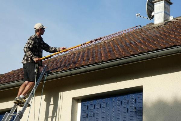 Couvreur qui nettoie une toiture par brossage